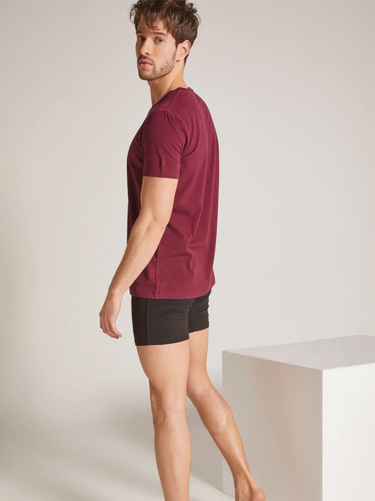 a person wearing a pink shirt and black shorts