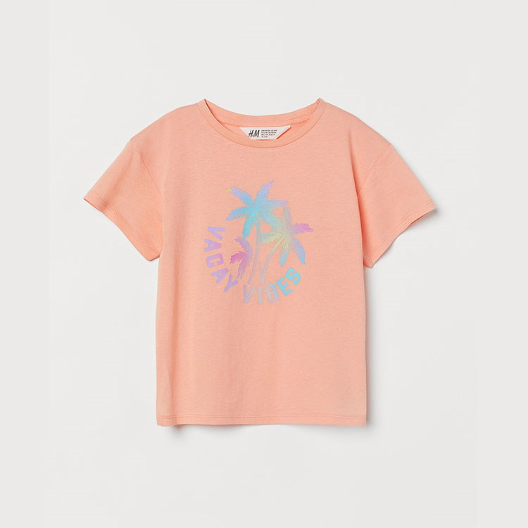 a pink t-shirt with a blue flower on it