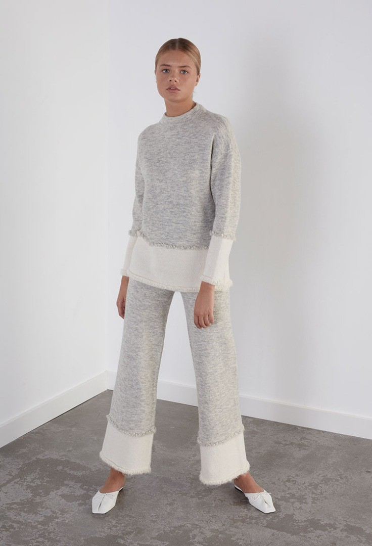 a person wearing a grey sweater and white pants