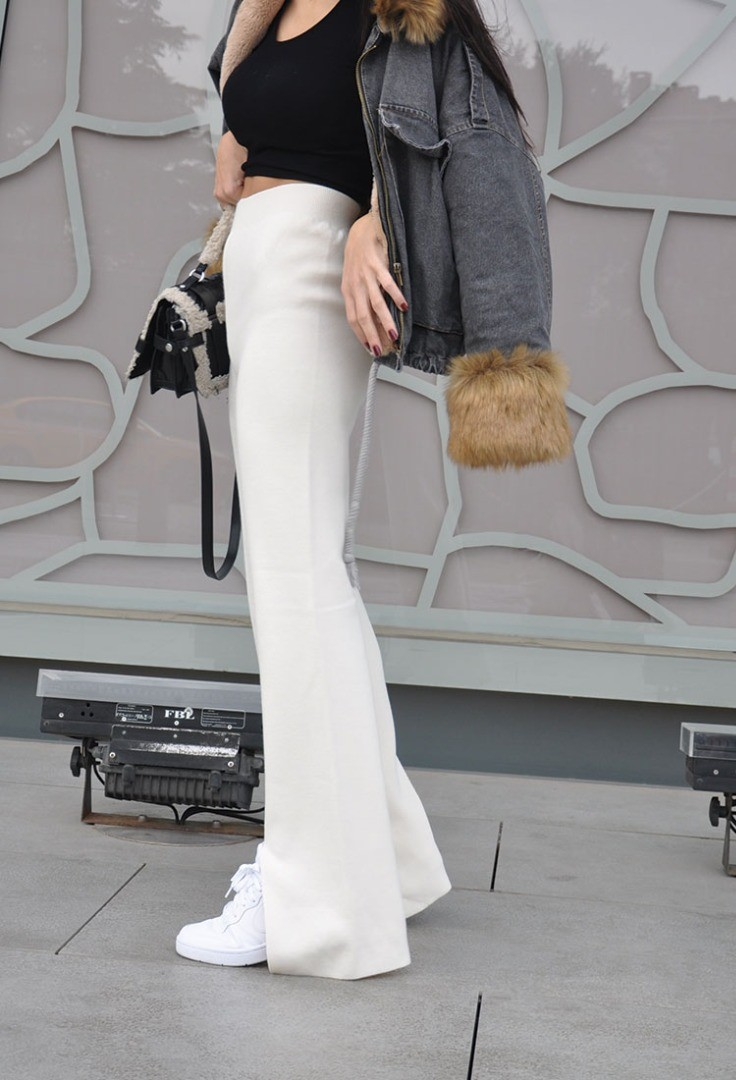 a woman wearing a black jacket and white pants