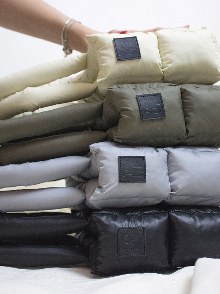 a person holding a bunch of pillows