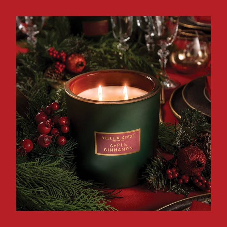 a candle in a green cup with red berries on a red surface
