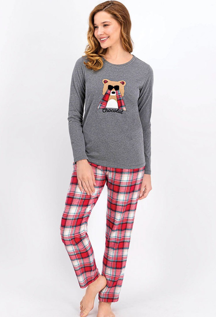 a woman wearing a grey sweater and plaid pants