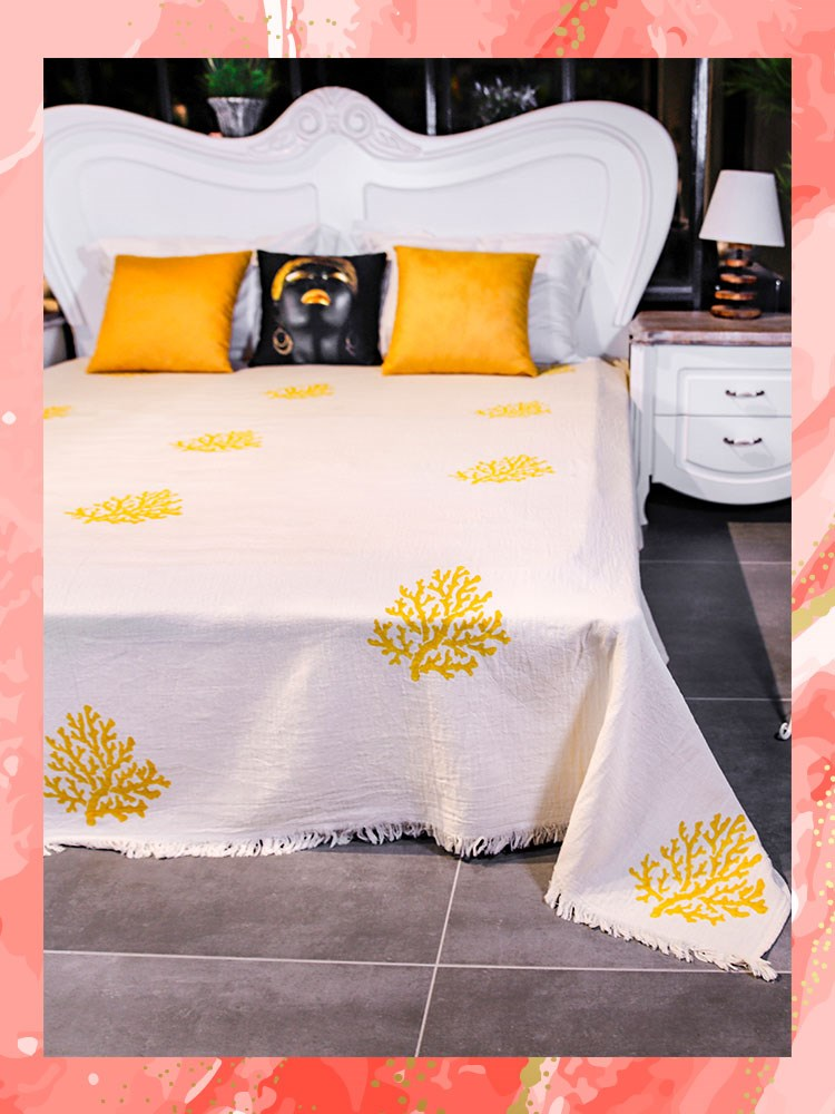 a bed with a white and yellow bed spread