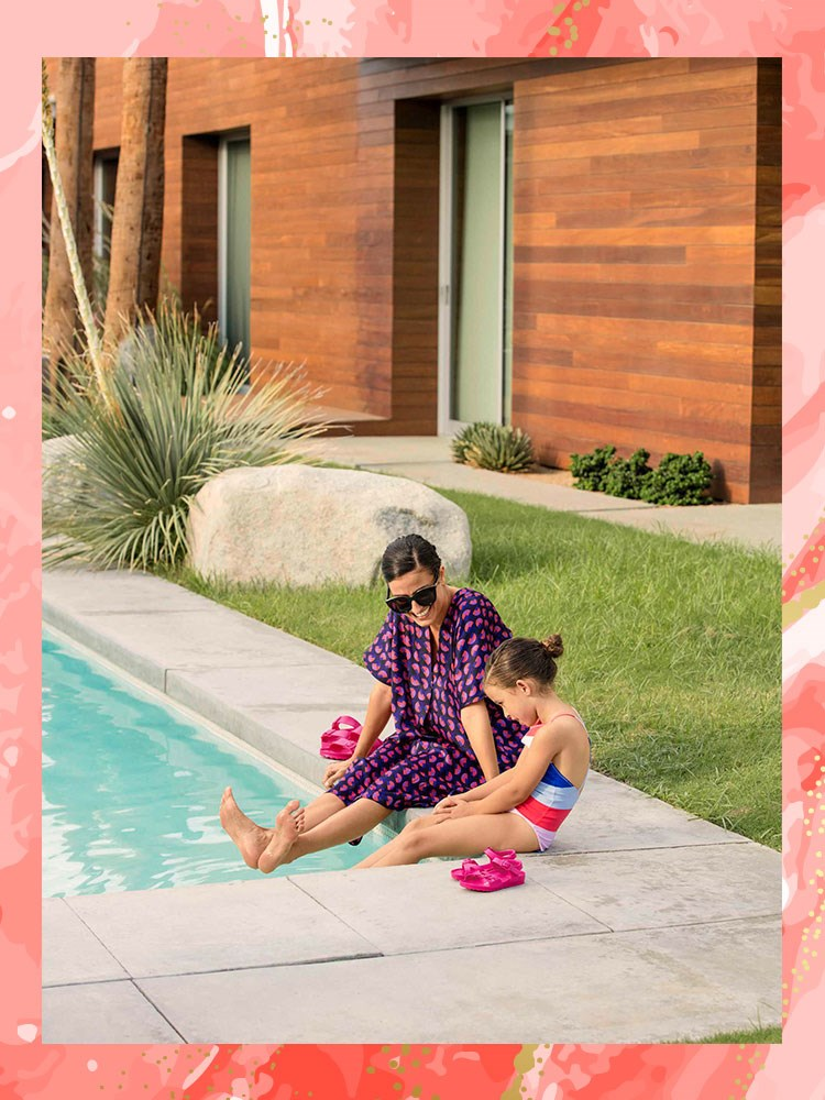 a person and a child sitting by a pool