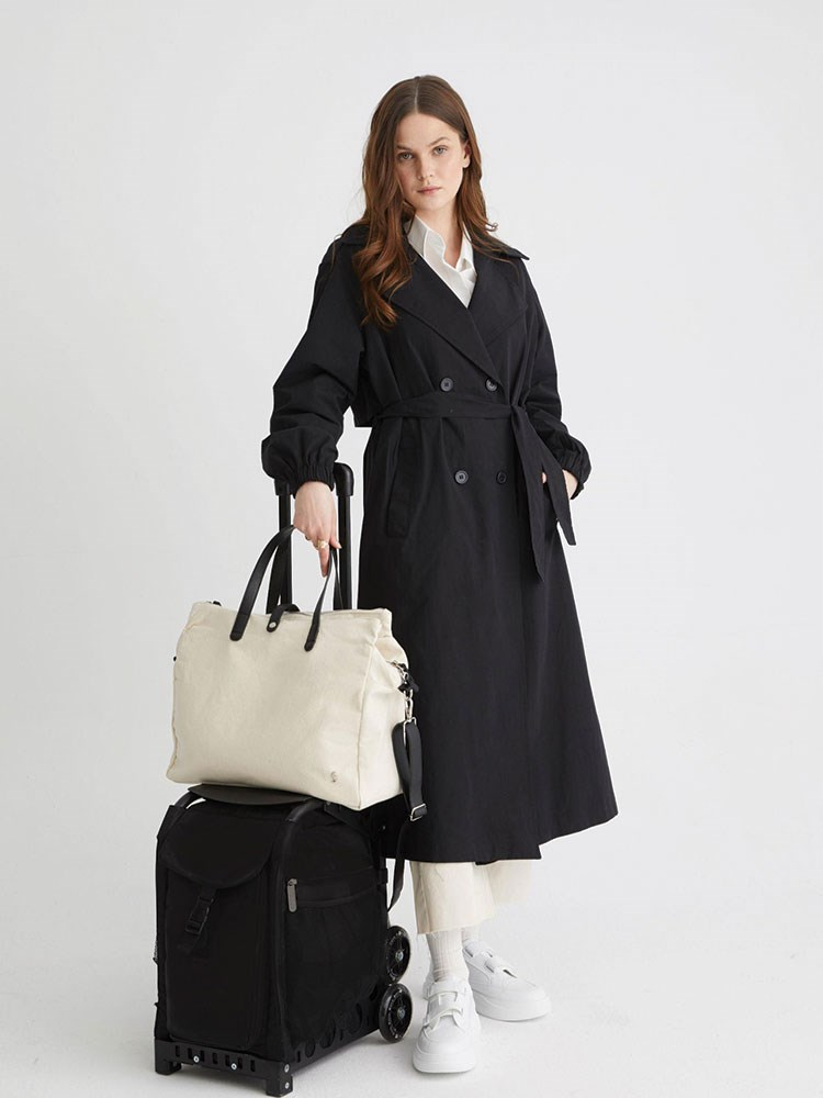 a woman in a long black coat holding a bag