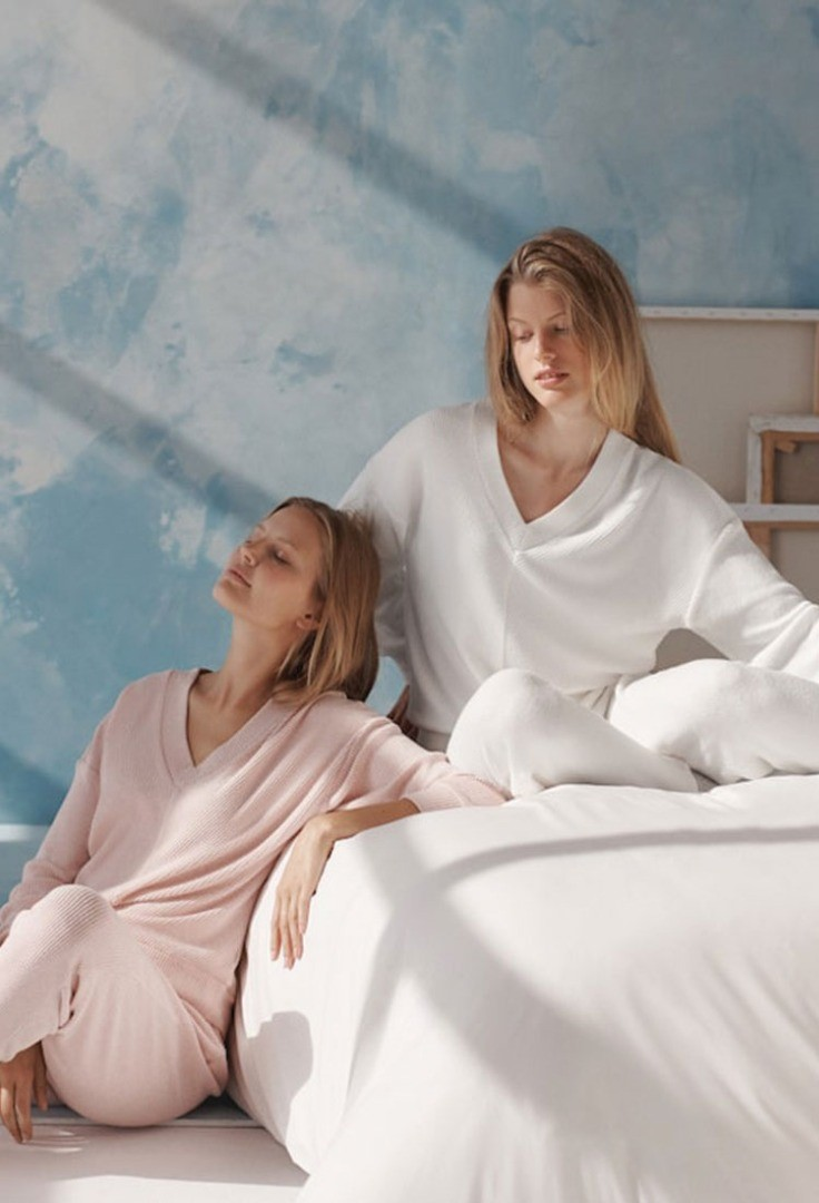 a couple of women sitting on a bed
