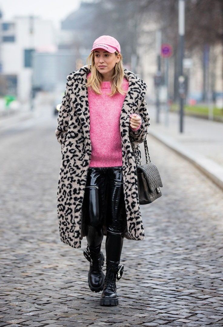 a woman wearing a pink hat and black boots walking on a street