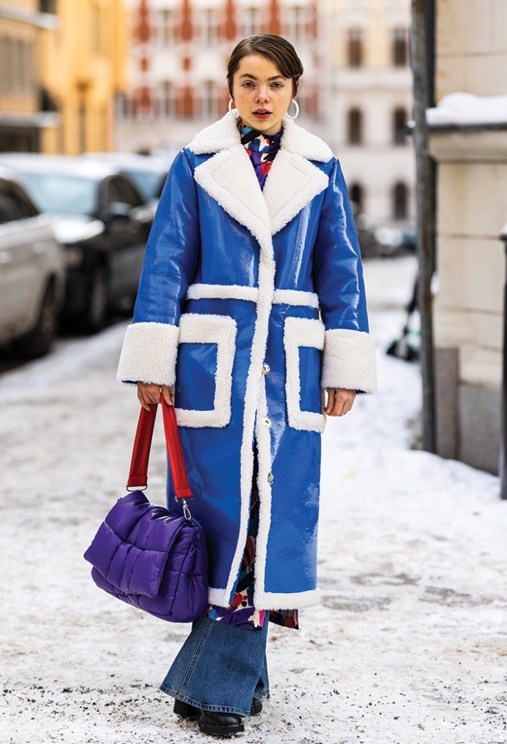 a person in a blue coat and a pink purse walking in the snow