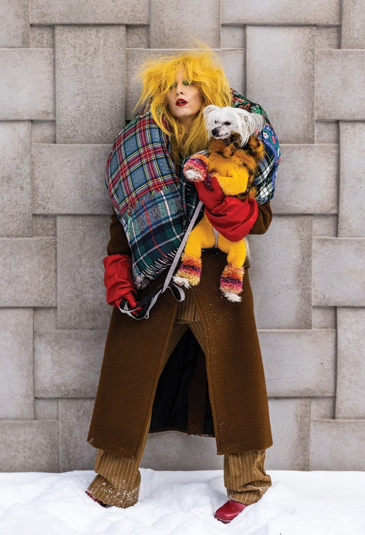 a person in a garment holding a dog