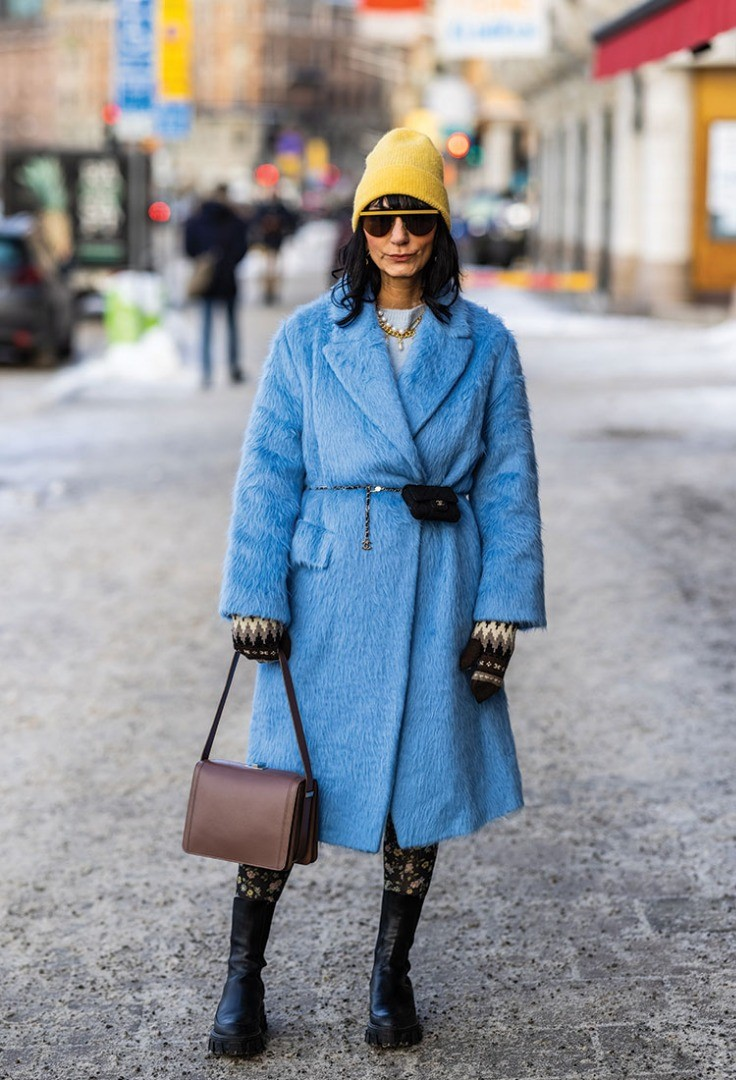 a woman in a blue coat and yellow hat walking down a street