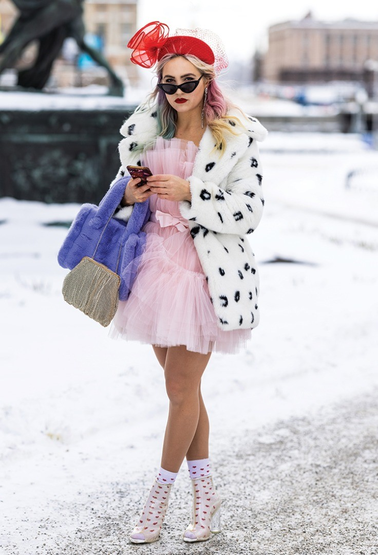 a woman in a pink coat and pink hat holding a phone