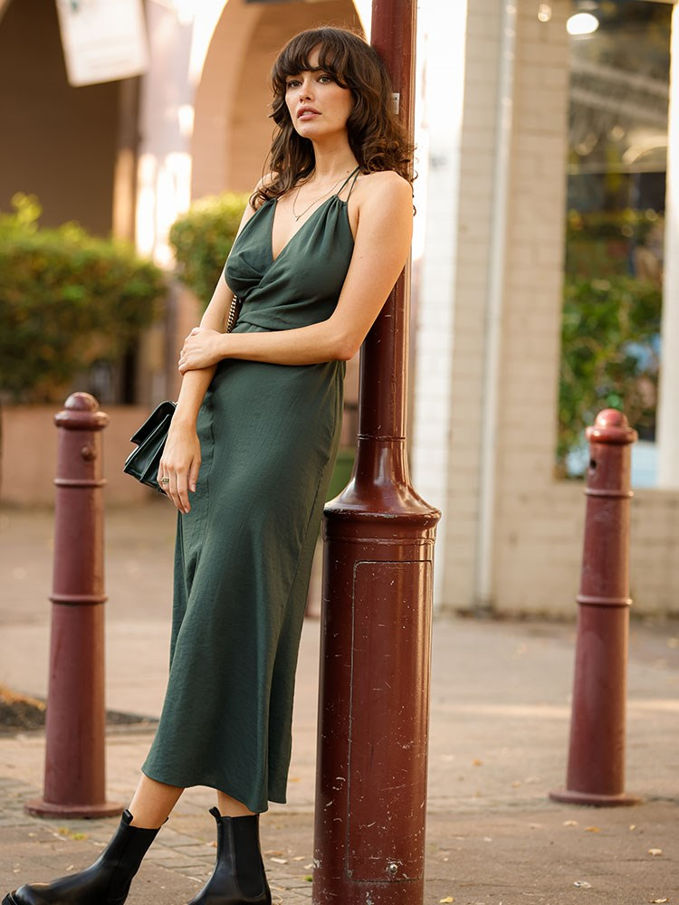 Sarah Stephens in a dress leaning against a pole