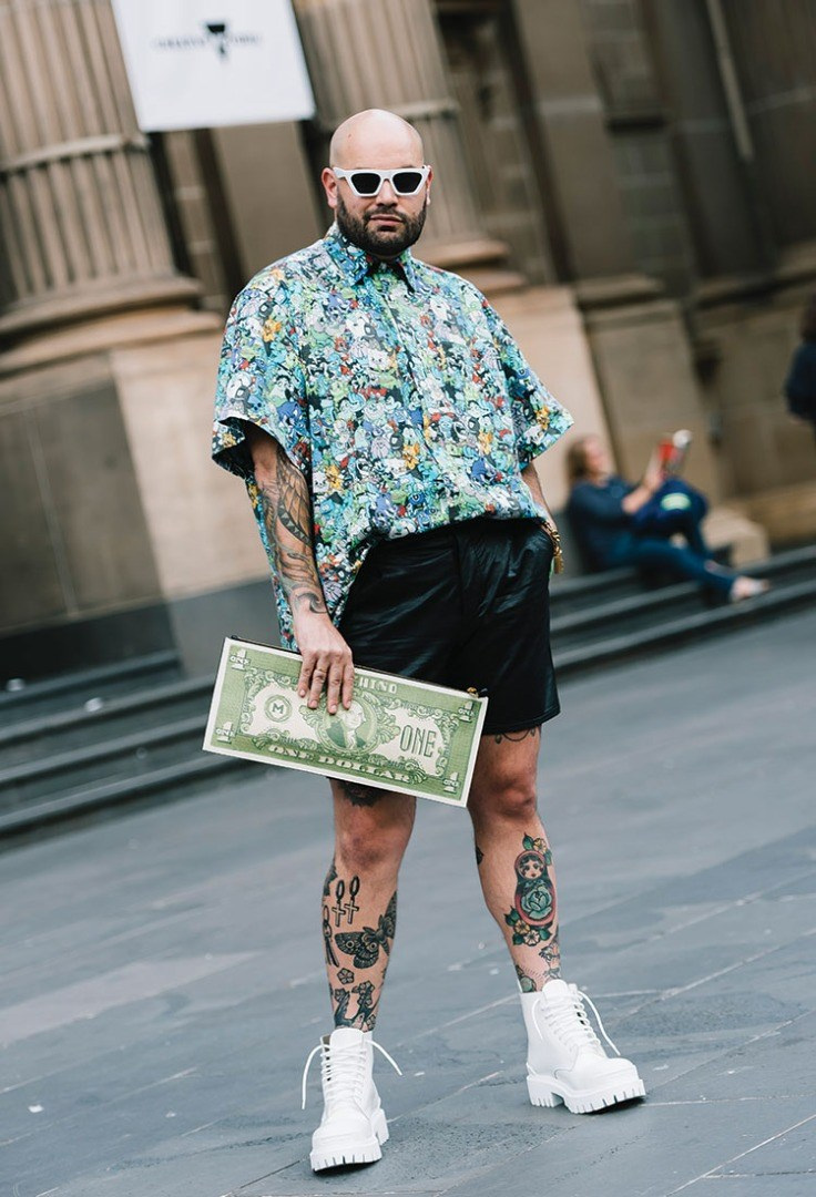 a man with tattoos holding a sign