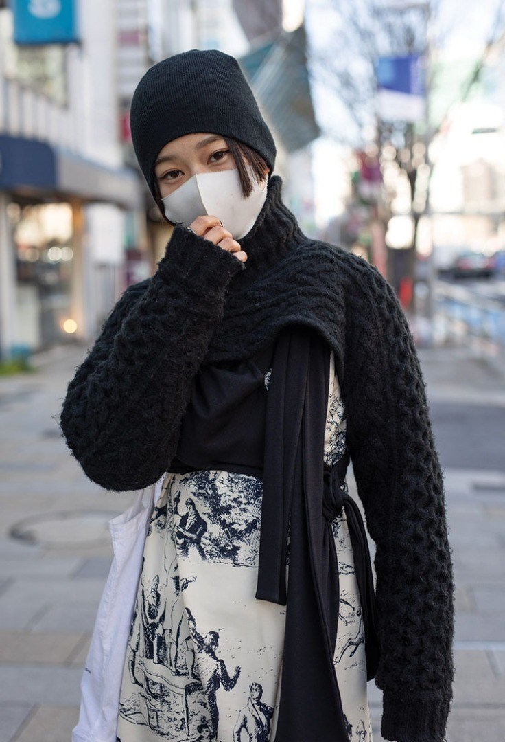 a person wearing a black head covering and a black scarf