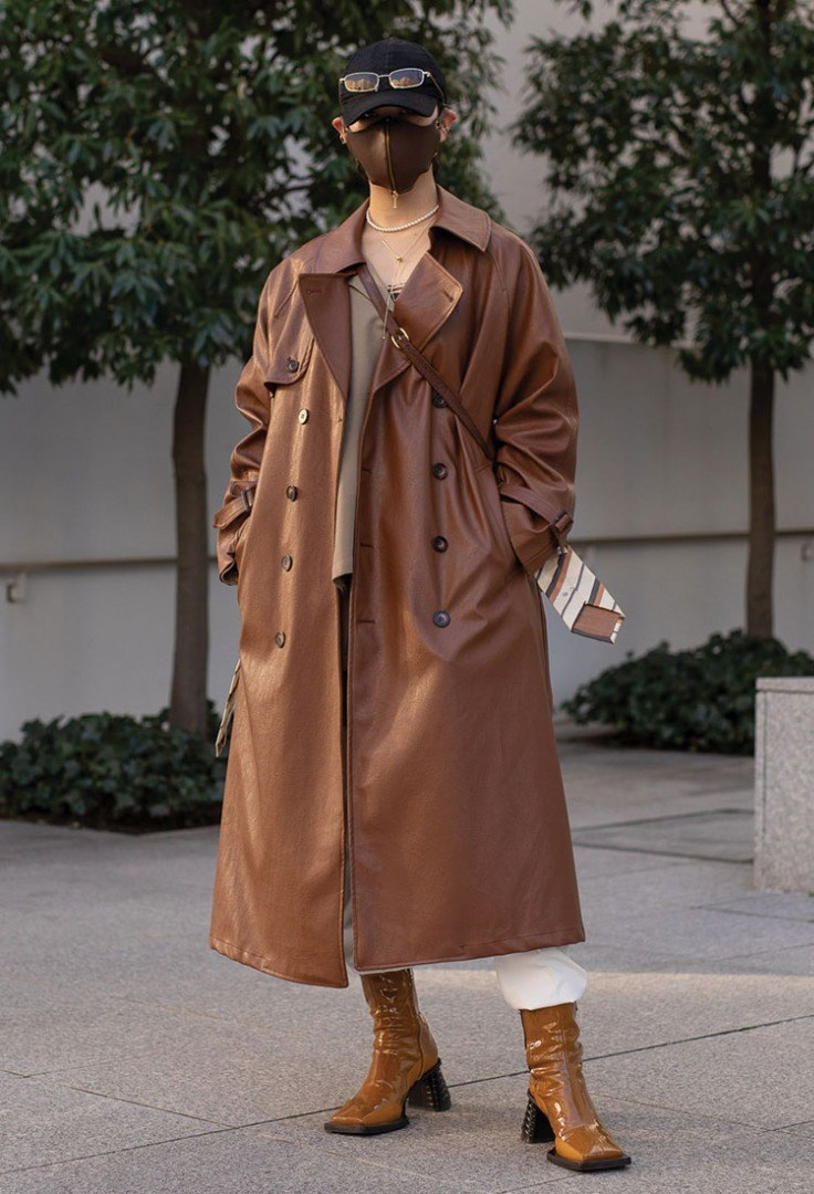 a person wearing a trench coat and hat
