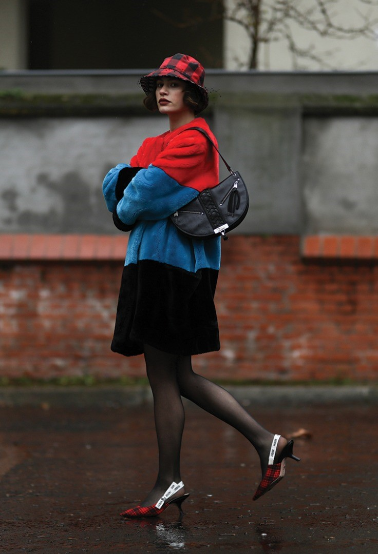 a person in a red shirt and black skirt holding a black purse