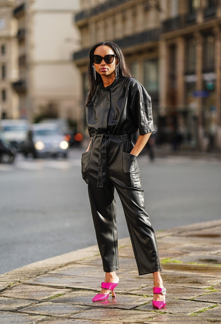 a person in sunglasses and a black jacket walking on a sidewalk