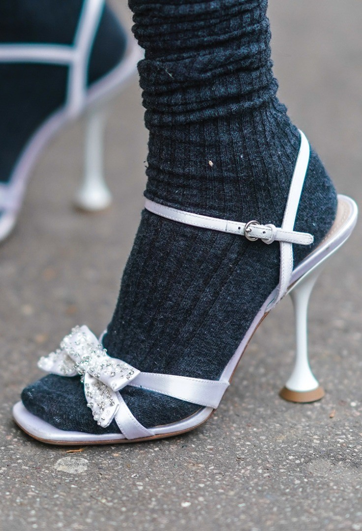 a person's feet wearing high heeled shoes