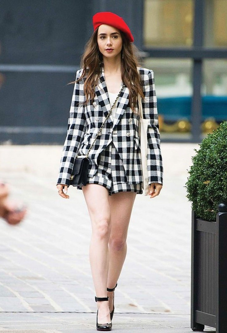 Lily Collins wearing a dress and a hat