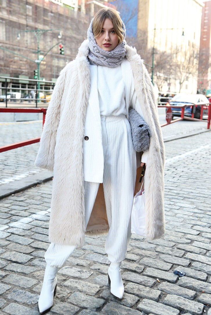 a person wearing a white coat and a scarf