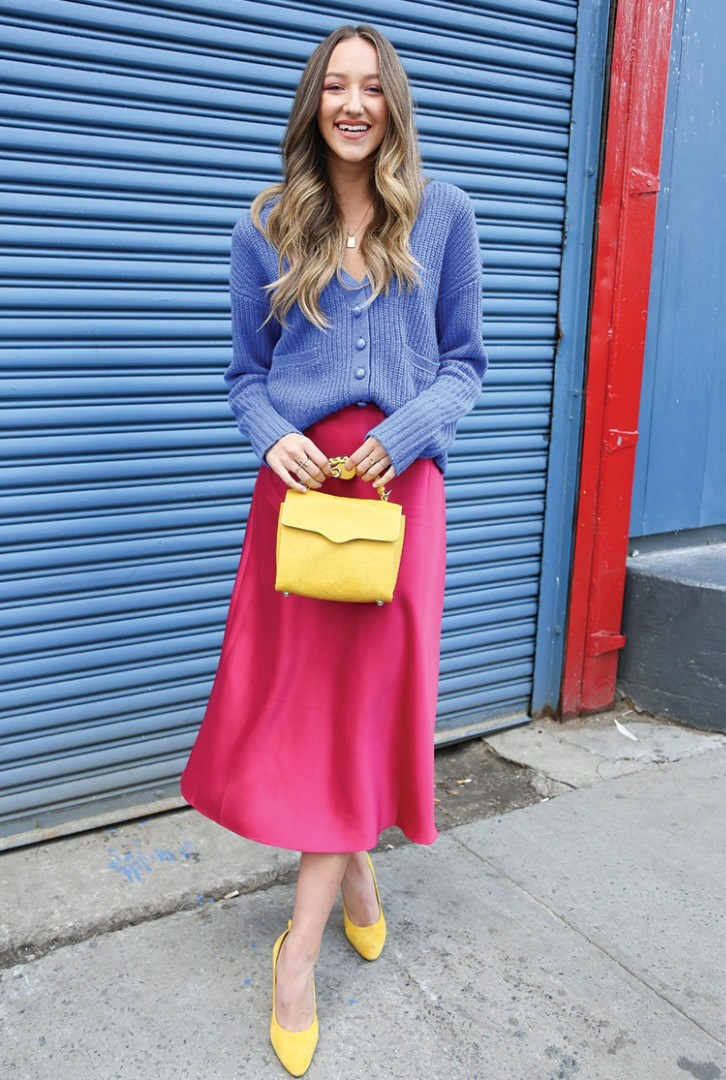 a woman in a blue shirt and yellow skirt