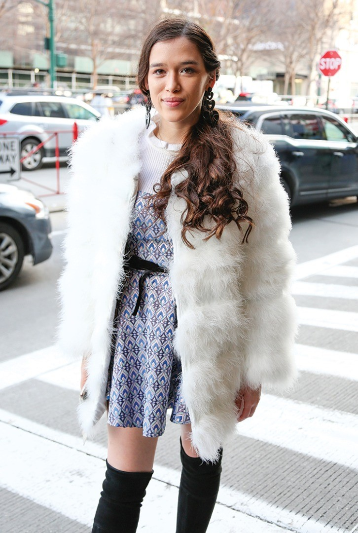 a woman in a fur coat and scarf standing on a street corner