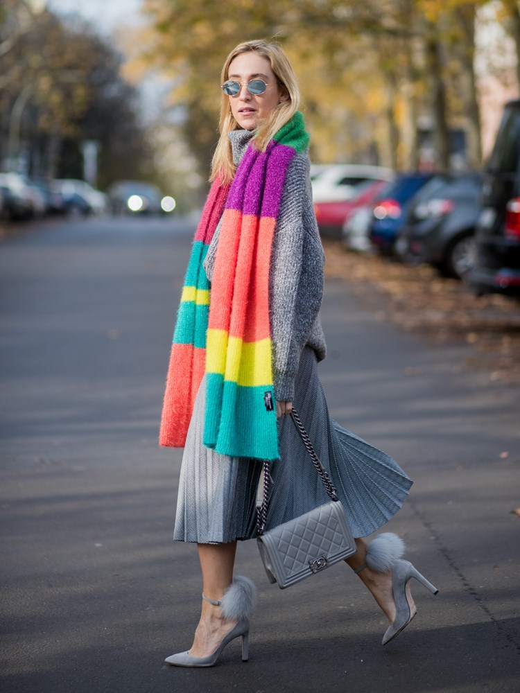 a woman in a colorful coat and sunglasses walking down a street