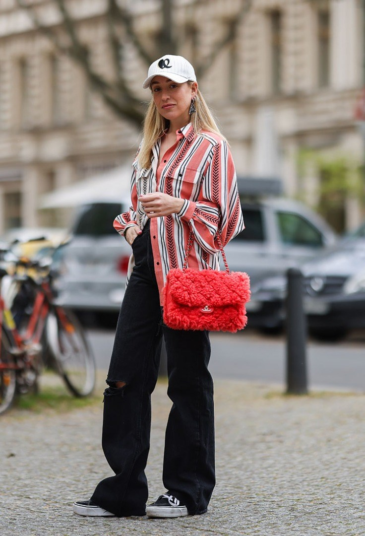 a woman in a red and white jacket holding a red purse