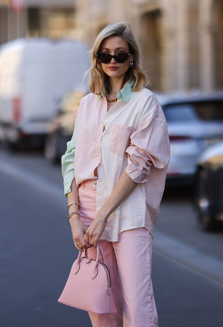 a woman wearing sunglasses and a pink jacket