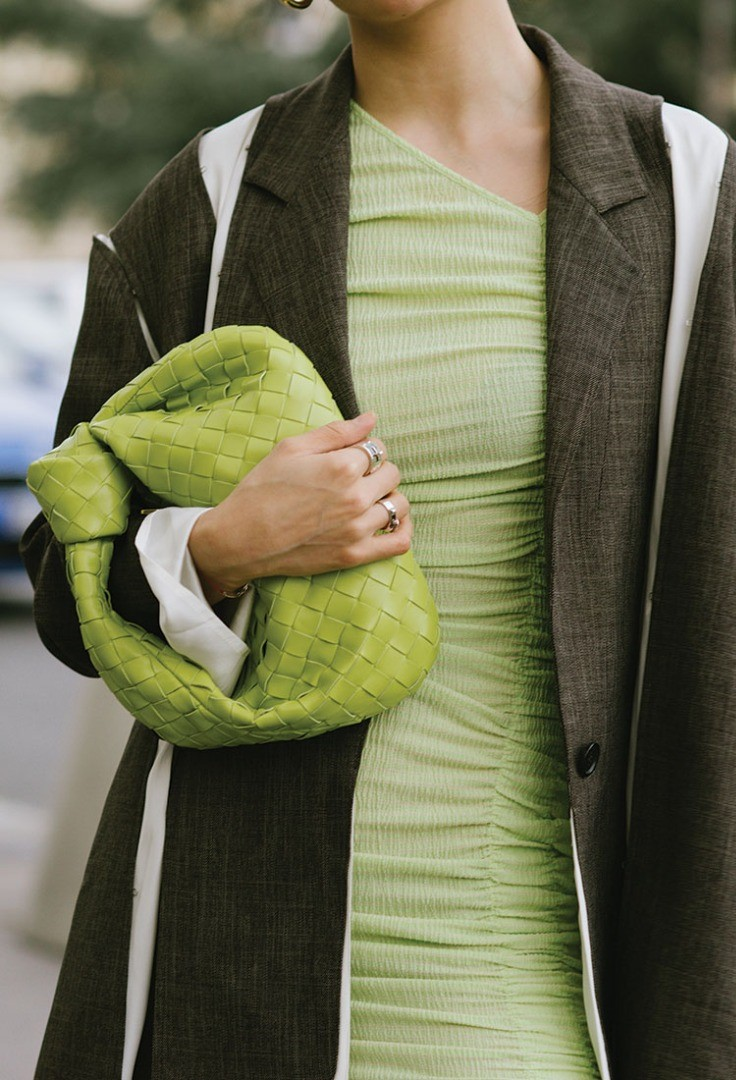 a person holding a green and yellow scarf over their head