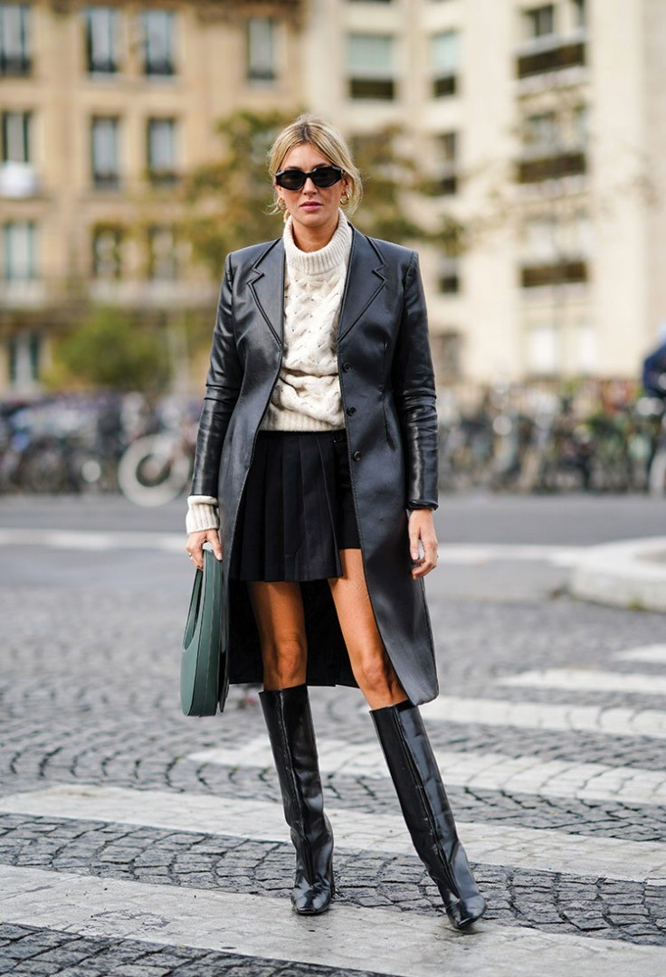 a person in a black coat and black boots walking on a brick road