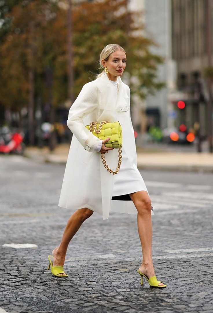 a person in a white dress holding a yellow ball