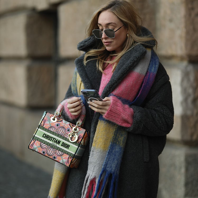 a woman holding a phone and a bag