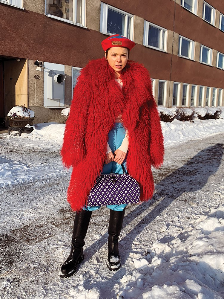 a person in a red and blue dress and a red hat standing in the snow