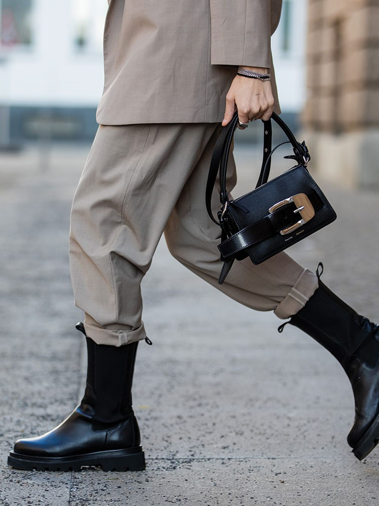 a person wearing a brown jacket and black boots