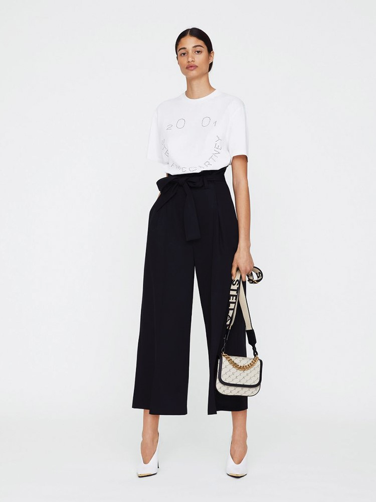 a person in a white shirt and black skirt holding a purse