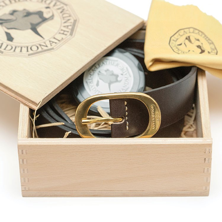 a box with a belt and a watch on it