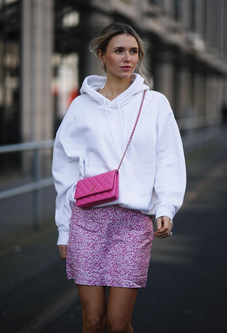 a woman wearing a white shirt and pink skirt