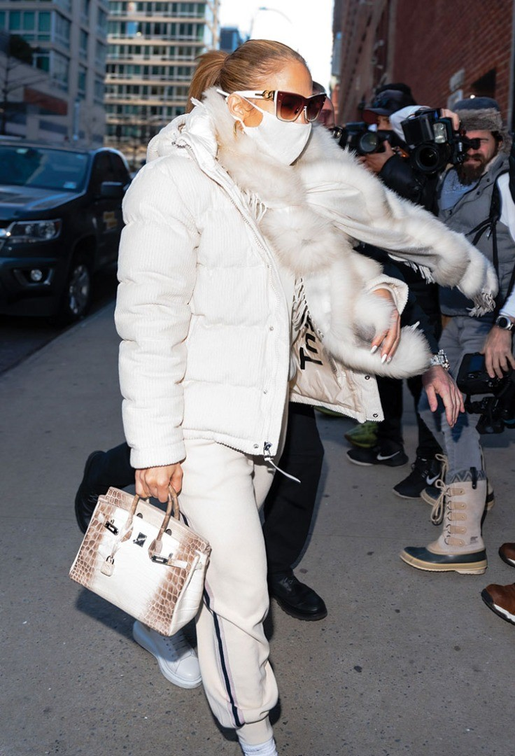 a person wearing a white coat and sunglasses walking with a camera