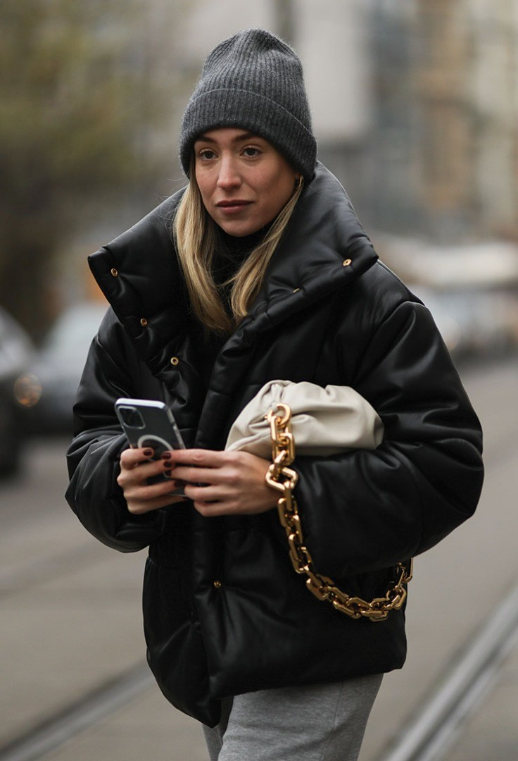 a woman wearing a black coat and holding a cell phone