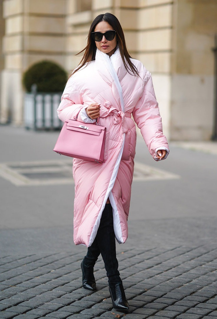 a woman wearing a pink coat and sunglasses