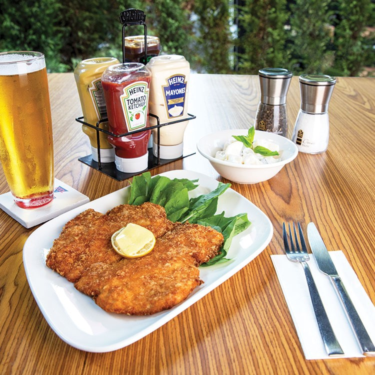 a plate of food and a glass of beer on a table