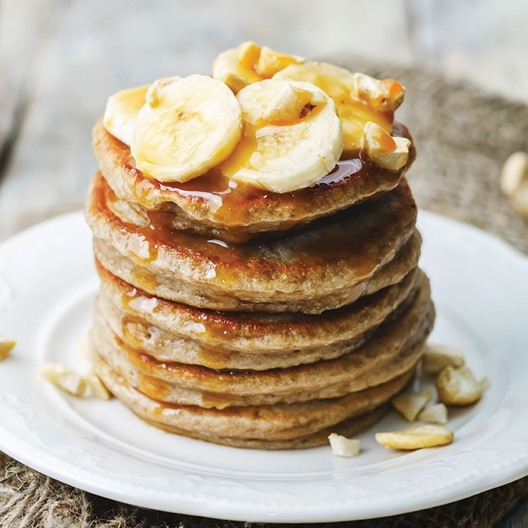 a stack of pancakes with bananas on top