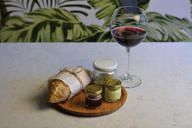 a glass of wine next to a tray of food and a glass of wine