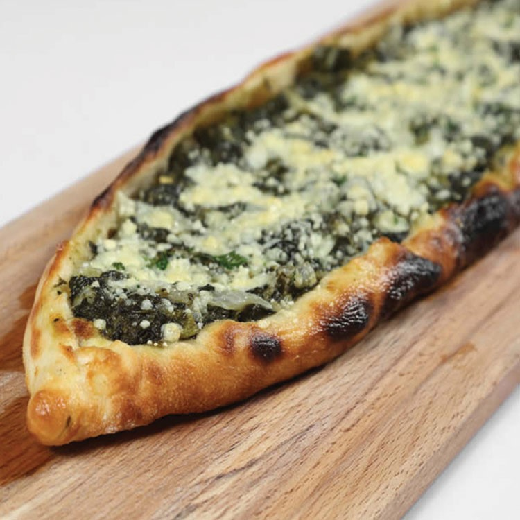 a pizza with cheese and spinach