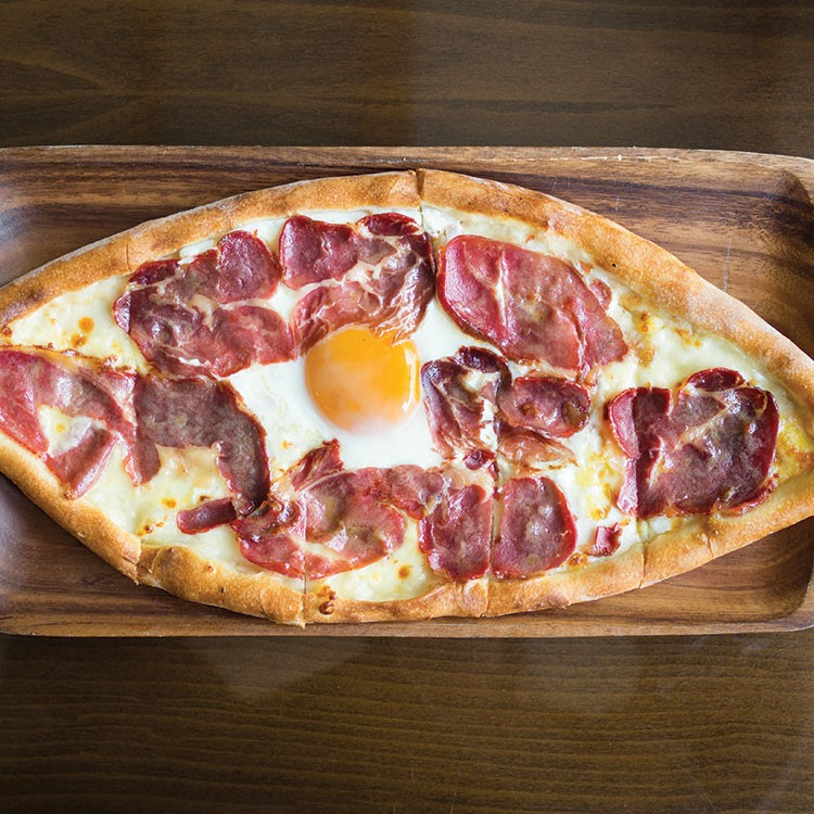 a pizza with eggs and bacon