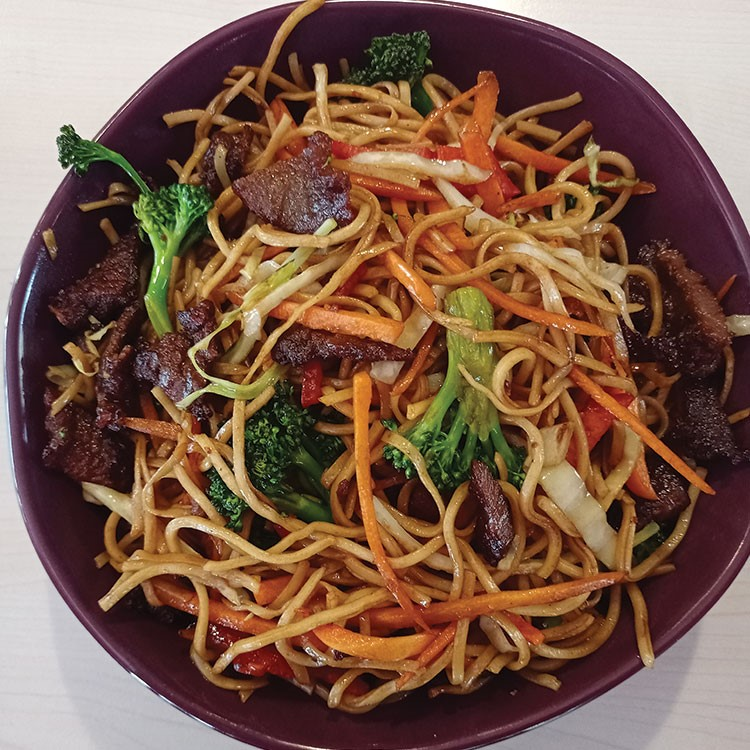 a bowl of noodles with meat and vegetables