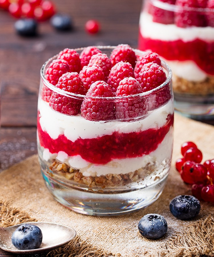a dessert with a red and white frosting and berries on top