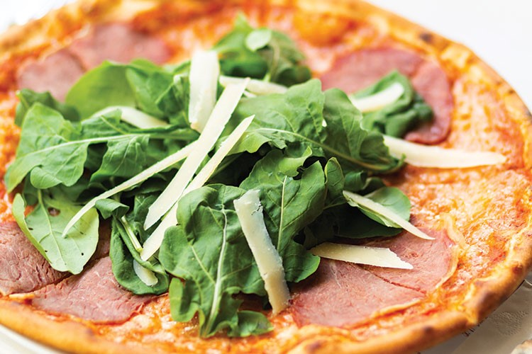 a pizza with basil on it